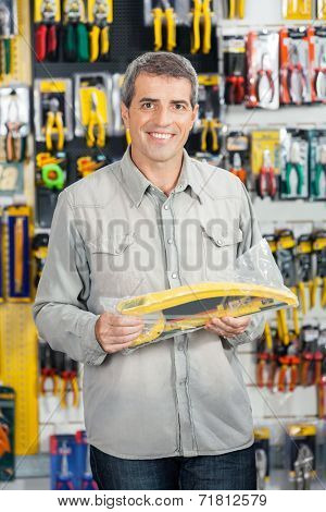 Portrait of happy mature man buying handsaw in hardware store