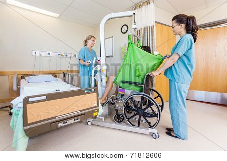 Female nurses transferring male patient from hydraulic lift to wheelchair in hospital