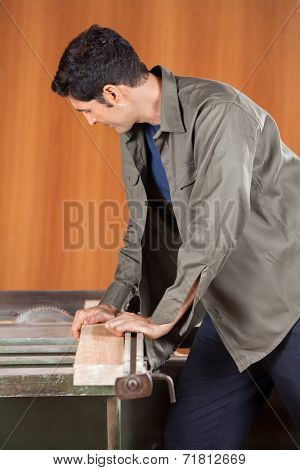 Young male carpenter cutting wood with tablesaw in workshop