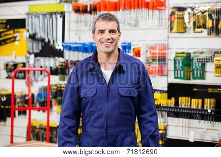 Portrait of confident worker smiling in hardware shop