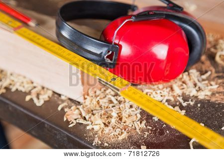 Closeup of wooden ruler and ear protectors in workshop