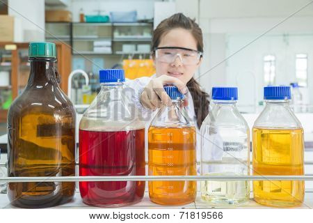 Asian Scientist Selecting Bottle In Shelf At Laboratory (focus At Bottle)