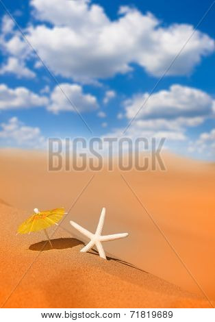 Starfish with cocktail umbrella on the sandy beach by the ocean