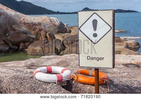 Orange And White Life Buoys On The Rock With Danger Sign Caution Around The Beach Shore.