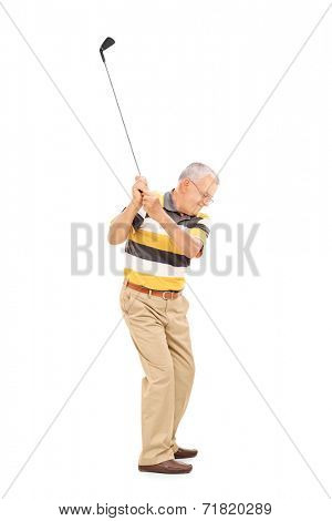 Profile shot of a senior swinging a golf club isolated on white background