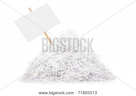 Signboard stuck in a pile of shredded paper isolated on white background