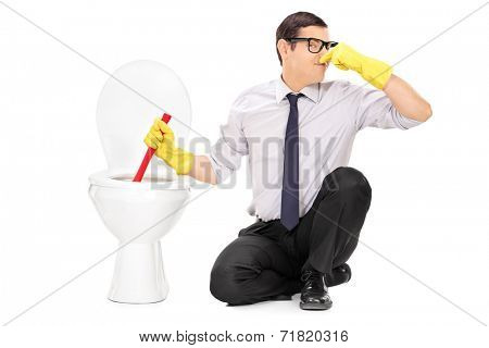 Young man unclogging a stinky toilet with plunger isolated on white background
