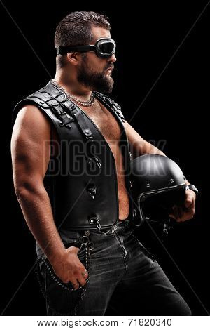Vertical shot of a male biker holding a helmet on black background