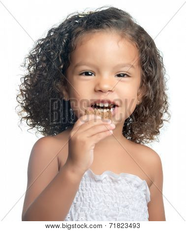 Small afro american girl eating a chocolate cookie isolated on white