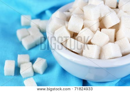 Refined sugar in bowl on color fabric background