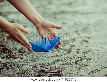 hands of a young woman with a paper boat by the lake in summertime (focus on the beat)