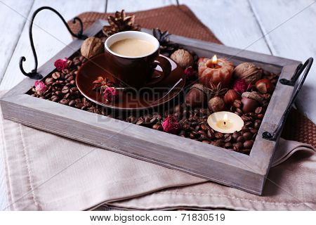 Candles on vintage tray with coffee grains and spices, cup of tea on color wooden background