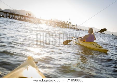 Woman Kayaking on Beautiful Peaceful Mountain Lake at Sunset.