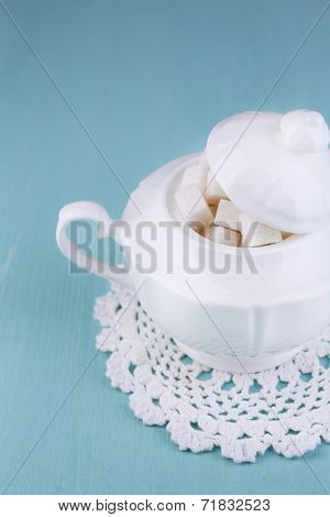 White refined sugar in sugar bowl on color wooden background