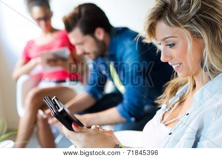 Young Business Woman Using Her Tablet, In The Background The Business People Use Tablet Too.