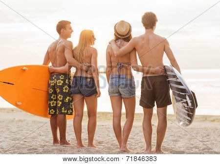 friendship, sea, summer vacation, water sport and people concept - group of smiling friends wearing swimwear with surfboards on beach from back
