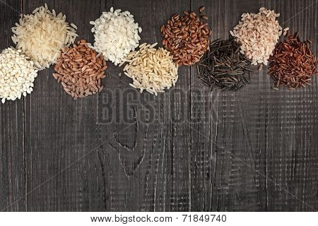 Border made of colorful varieties of whole grain rice in a black wooden surface background