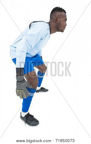 Full length side view of a concentrated goal keeper over white background
