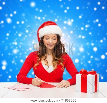 christmas, holidays, celebration, greeting and people concept - smiling woman in santa helper hat with gift box writing letter or sending post card over blue snowy background