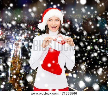 christmas, winter, happiness, holidays and people concept - smiling woman in santa helper hat with small gift box and stocking over snowy city background