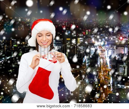 christmas, winter, happiness, holidays and people concept - smiling woman in santa helper hat with small gift box and stocking over snowy night city background