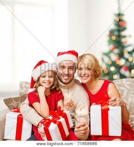 family, christmas, x-mas, happiness and people concept - smiling family in santa helper hats with many gift boxes and bengal lights