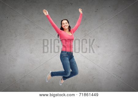 happiness, freedom, movement and people concept - smiling young woman jumping in air over concrete wall background