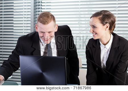 Smiling Co-workers Using Laptop