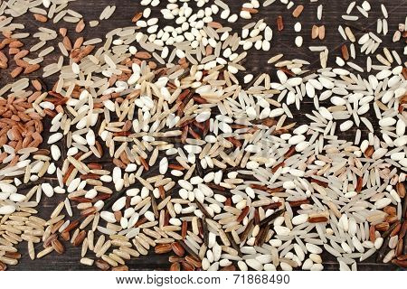colorful blend of several varieties of whole grain rice in a rustic wooden surface background