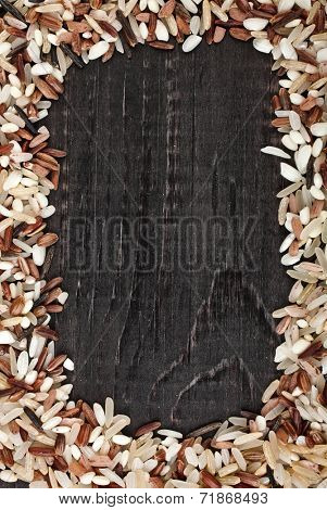 Frame made of colorful blend several varieties of whole grain rice in a rustic wooden surface background