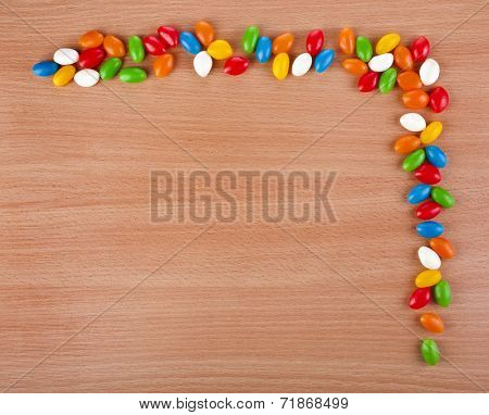 Colored  JellyBeans spilled on surface wooden table. top view