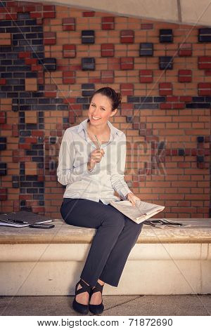 Attractive Woman Sitting On A Wall Bench Laughing