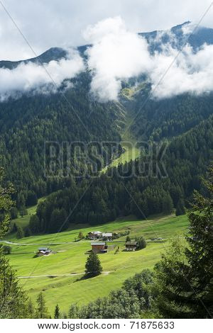 PRAYON, SWITZERLAND - AUGUST 30: Small village at the bottom of forest on hill, with low hanging clouds. The area is a stage of the popular Mont Blanc tour. August 30, 2014 in Prayon.