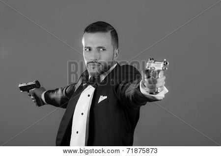 Handsome young man holding two guns