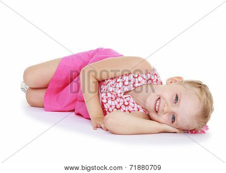 Cute little girl smiling lying on the floor