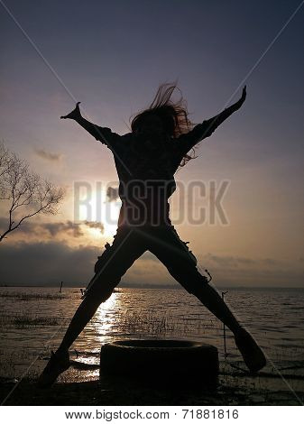 Silhouette Of Young Woman Jumping.