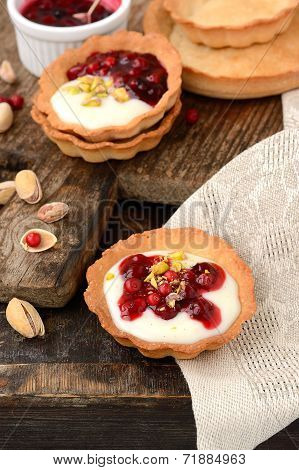 tartlets with cream, berry sauce and pistachios