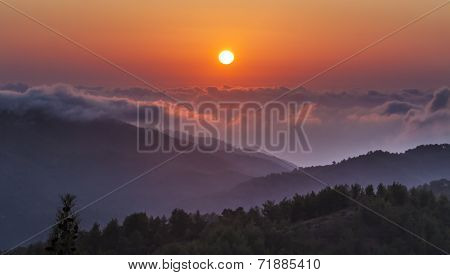 The sun sets above clouds at altitude in the Troodos Mountains