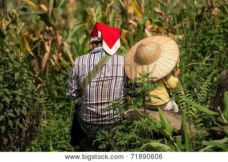 Red Dao Mother and Child resting in field