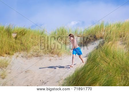 Happy Child Jumping In The Dunes