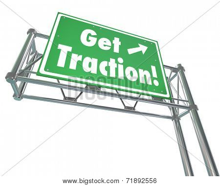 Get Traction words on a green road or freeway sign illustrating the gaining of momentum or making progress with acceptance or popularity