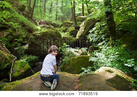 Cute Boy Playing On The Rocks Near A Scenic Waterfall