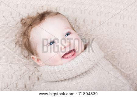 Cute Gunny Baby Girl In A Knitted Sweater On A Knitted Blanket