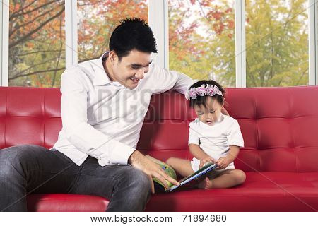 Father And His Child Reading A Book
