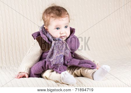Funny Baby Girl In A Warm Purple Jacket On A Knitted Blanket