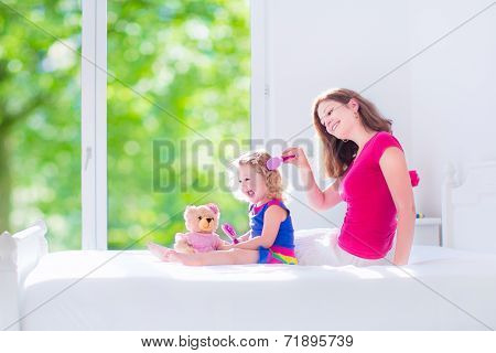 Mother And Daughter Brushing Hair