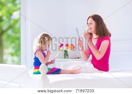 Mother And Daughter Applying Make Up