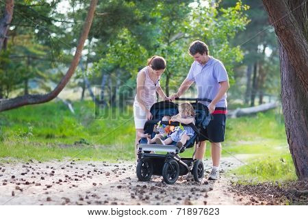 Young Family Hiking With Two Kids In A Stroller
