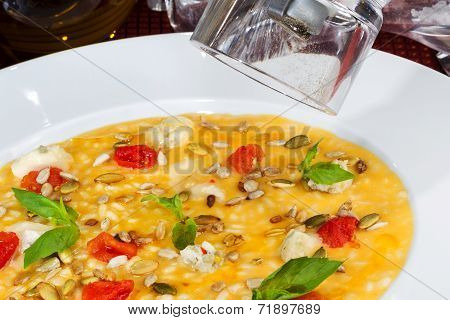 Rice Soup With Pumpkin Seeds, Cereals And Tomatoes In A White Bowl.
