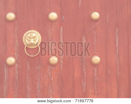 Ancient Red Wooden Gate With Lion Door Knocker In Vintage Style